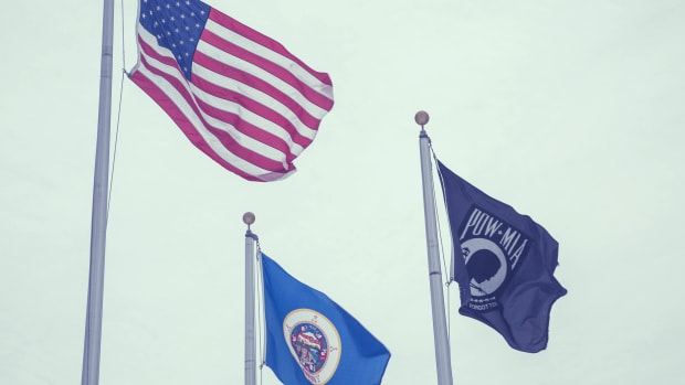 American flag, Minnesota flag, and POW flag