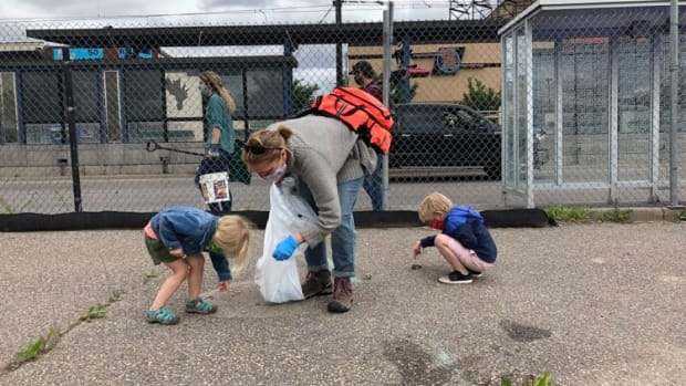 """Longtime St. Paul resident Angela Elder Woodbury came to clean debris left by riots in Midway with her 5- and 3-year-old. """"It's a good way to learn how to help when they can,"""" she said."""