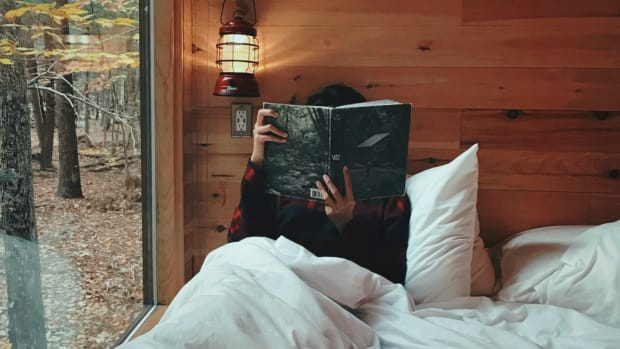 A person sitting in bed in a cabin, reading a book.