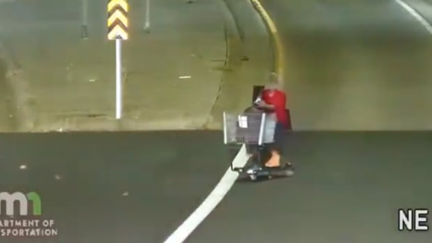 Woman driving shopping cart on highway.