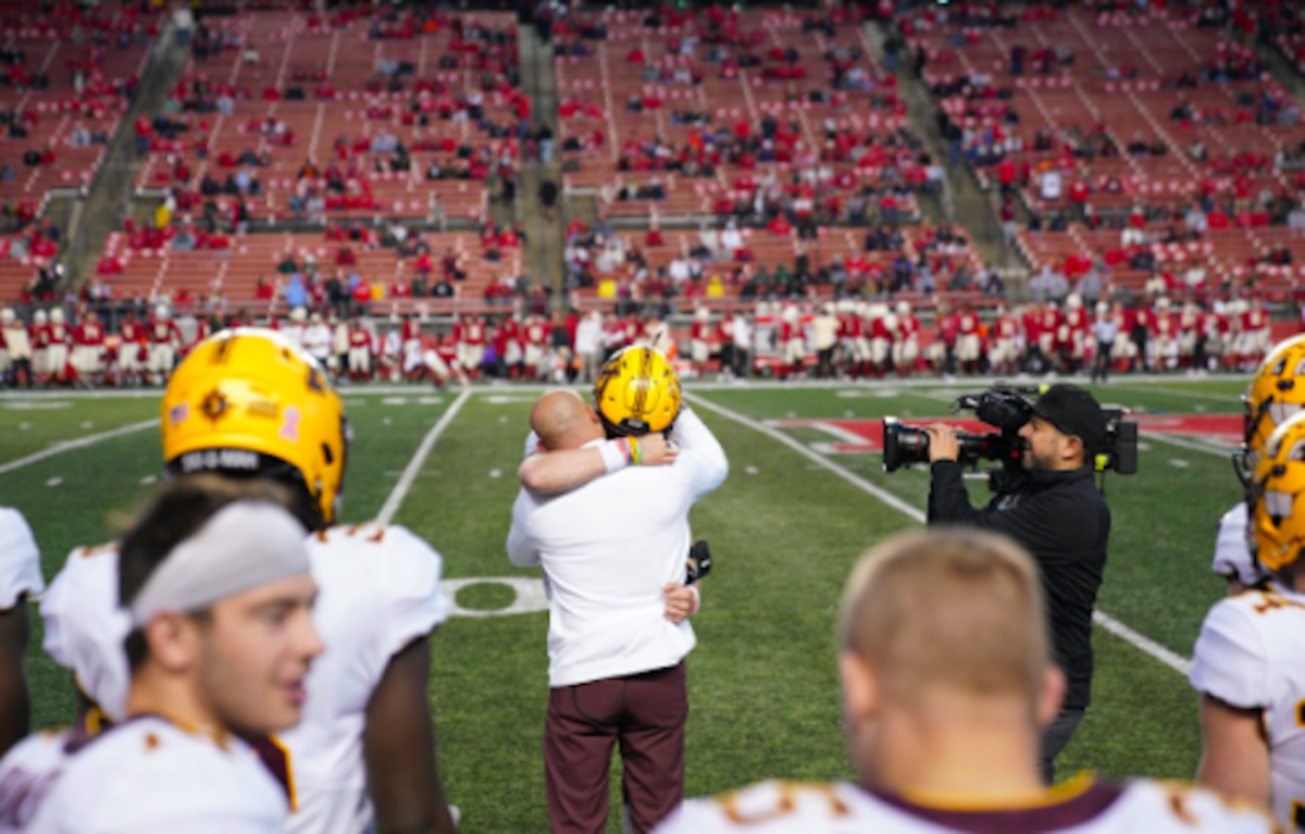 Casey O'Brien and P.J. Fleck embrace after O'Brien made his college football debut at Rutgers.