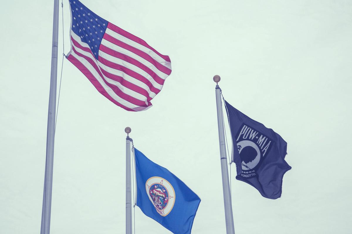 American flag, Minnesota flag, and POW flag