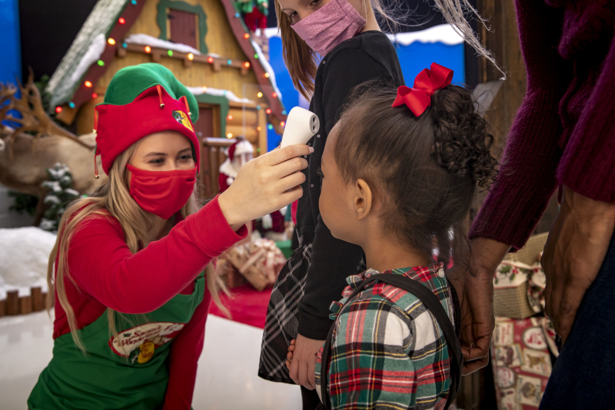 One of Santa's elves takes the temperature of a visitor prior to entry. Photo courtesy of Cabela's.