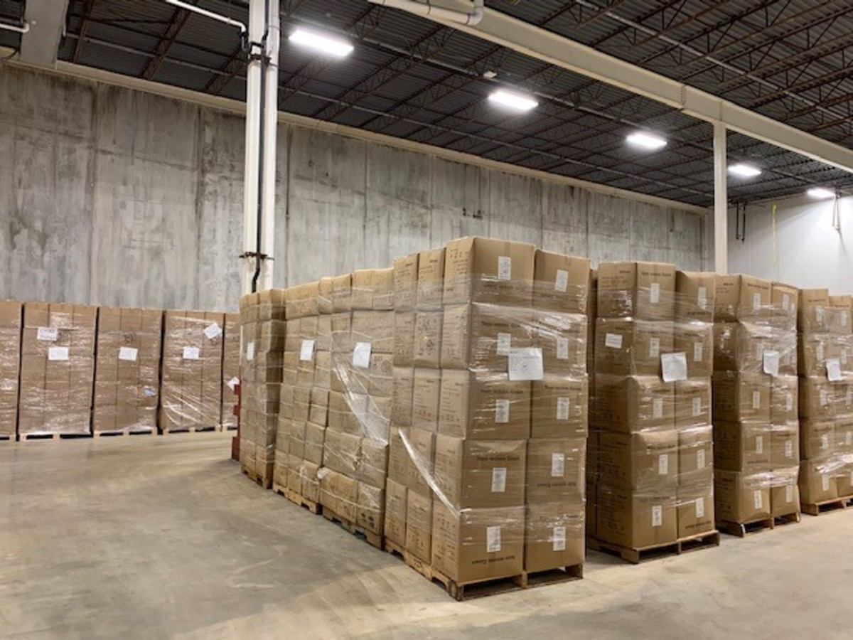 Boxes of PPE wrapped and stacked on pallets inside the warehouse.