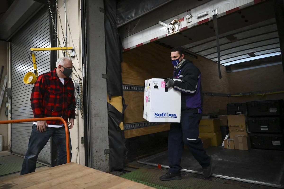 Gov. Tim Walz looks on as the first shipments of the COVID-19 vaccine arrive in Minnesota Monday morning.