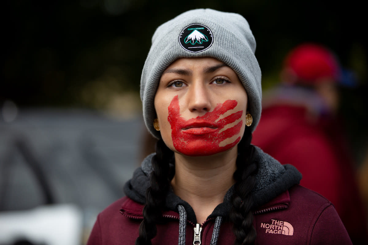 A participant in the Greater Than Fear rally in Rochester. A red hand across the mouth has become a symbolic representation of violence that affects Indigenous women.