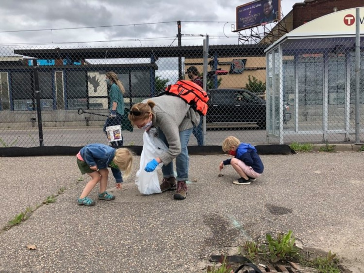 "Longtime St. Paul resident Angela Elder Woodbury came to clean debris left by riots in Midway with her 5- and 3-year-old. ""It's a good way to learn how to help when they can,"" she said."