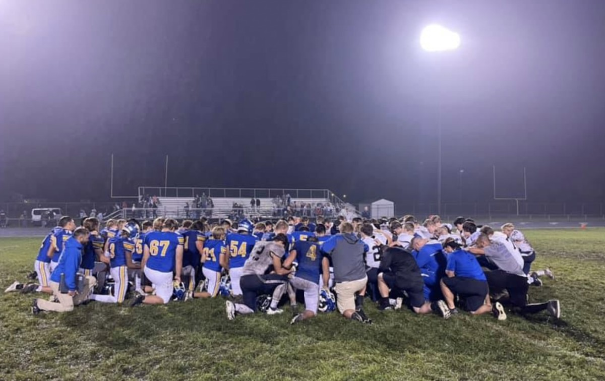 Waseca and St. Peter players hold a prayer at midfield after Brad Wendland's collapse.